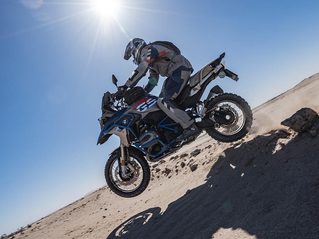 Motorradfahrer unter der Sonne in der Wüste Namibias mit Afrikabiker