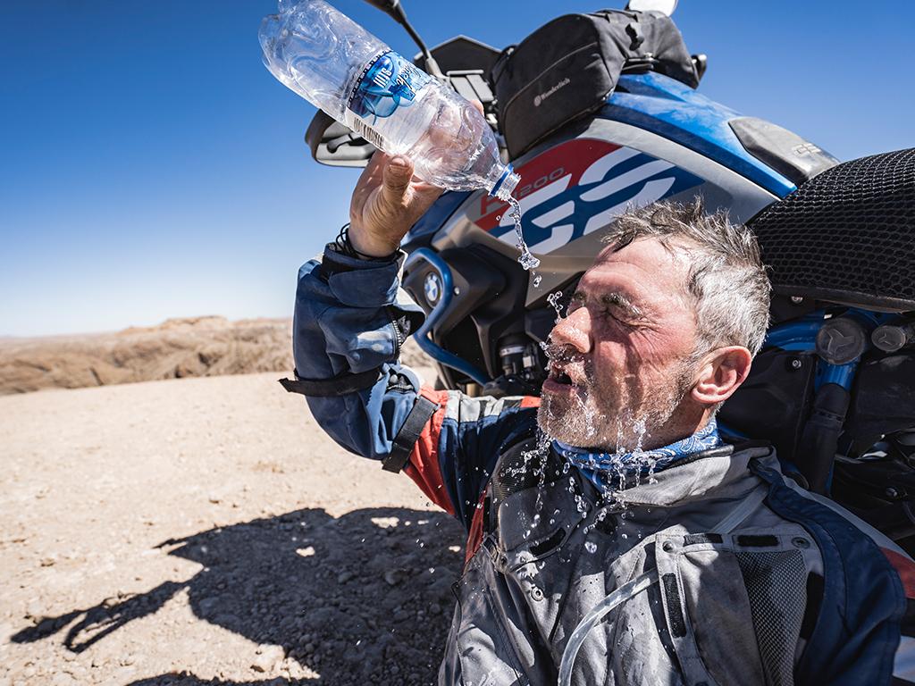 Afrikabiker Motorradfahrer in der Wüste mit Wasser